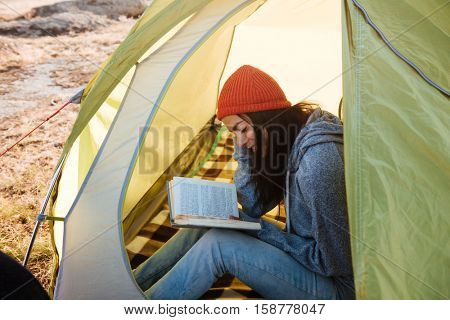 Woman with book in tent. cropped image.