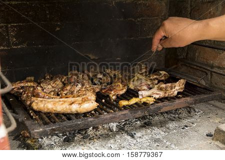 Hand with fork aranging meat on barbecue