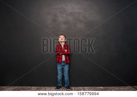Image of pretty little boy standing over chalkboard and looking up