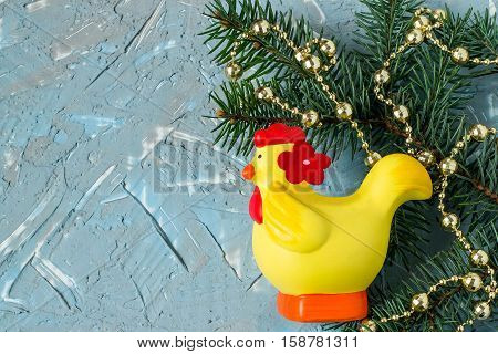 Festive Christmas background with fir branches beads on the textured surface of the blue and gray putty. Rooster - symbol of the new year 2017 on the eastern calendar free space for text