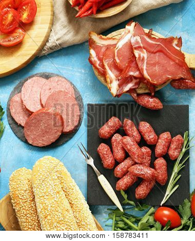 Lunch picnic table deli meats (sausage, salami, parma, prosciutto) bread and vegetables, top view