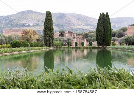 Trees with lake reflection and mountain at hadrian villa, adriana is a large roman archaeological complex at tivoli, Italy
