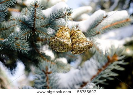 Christmas background with golden bells on the Christmas tree