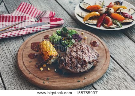Grilled beef steak cooked on barbecue, closeup on dark rustic wood background. Fresh juicy roasted red meat on round wooden board, with corn and vegetables. Restaurant food, delicious dish