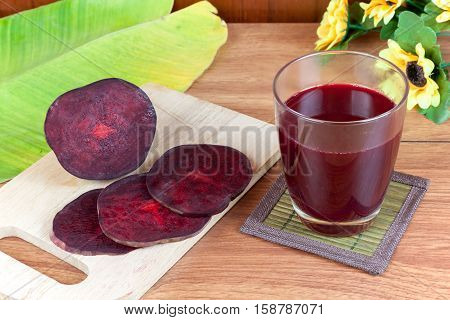 Fresh slices red beetroot and beetroot fruit juice in glass a wood background