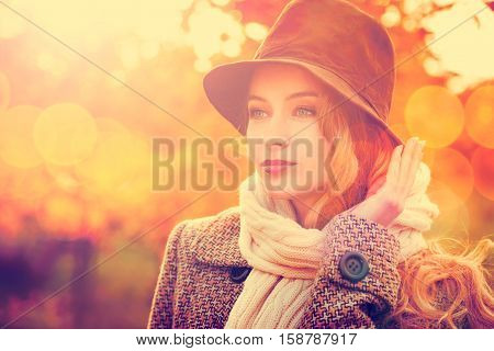 Fashion Woman in Hat and Scarf on Orange and Red Autumn Background in Sunny Day. Beatiful Girl Portrait. Female in Fall Concept. Toned Photo with Bokeh and Copy Space.