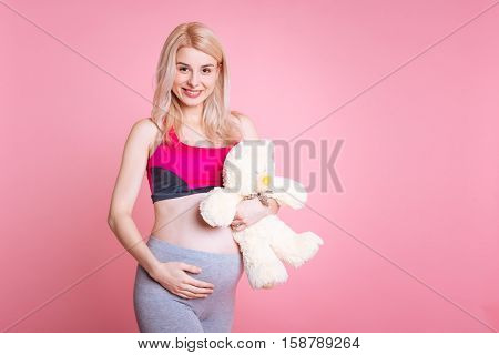 Good news. Cute smiling sportswoman stroking a baby belly holding a toy bear in the left hand looking in the camera, isolated on pink background