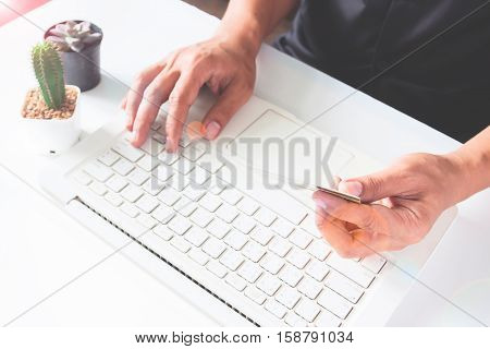Hands holding credit cards and using laptop. Online shopping