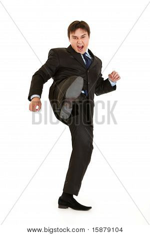 Very angry young businessman hard kicking isolated on white poster