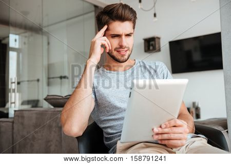 Picture of confused bridal man dressed in grey t-shirt sitting on chair and holding tablet while holding his head with hand.