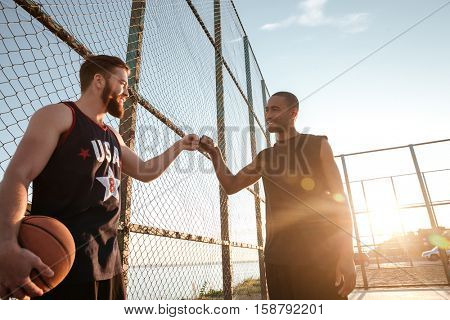 Two happy sportsmen fist bumping before starting basketball game at the playground