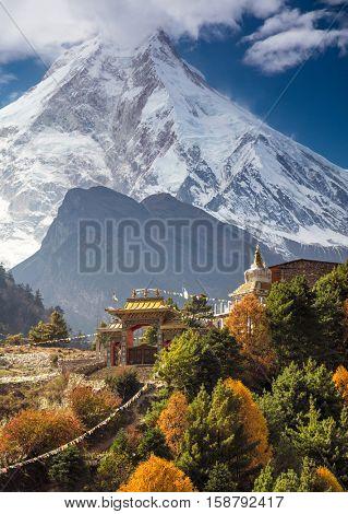 Traditional Buddhist monastery and Manaslu mount in Himalayas, Nepal.  Autumn, view from Manaslu circuit trek