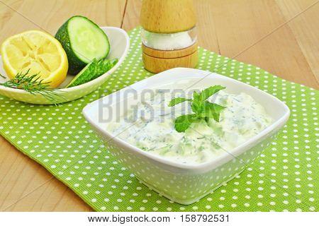 Tzatziki sauce. Greek cucumber yogurt dip in white bowl over wooden table.
