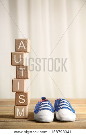 Wooden cubes with word autism and baby shoes on light background