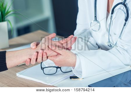 Female patient at orthopedic medical exam in doctor's hospital office traumatology and medical consultation for hand wrist injury