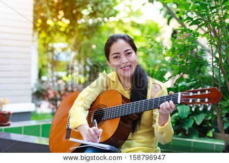 Beautiful Songwriter Writing On Note Paper With Acoustic Guitar Near By.
