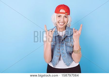 Like a young. Overjoyed pretty senior woman laughing and gesturing while standing against isolated blue background.