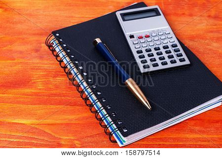 Lying on the table a black diary pen and calculator. Business accessories