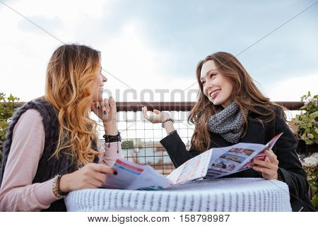 Two models in cafe. with map. in coats. talk