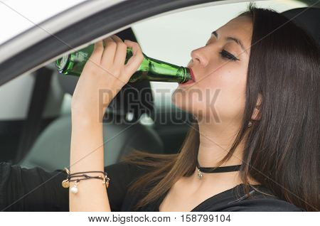 Closeup young woman sitting in car holding green beer bottle and drinking, as seen from outside drivers window, female driver concept.