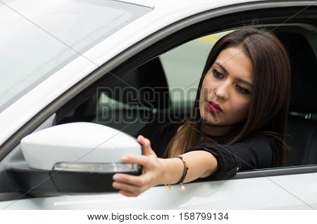 Closeup young woman sitting in car adjusting side mirror, as seen from outside drivers window, female driver concept.