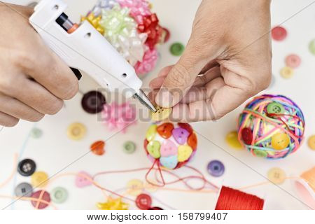 closeup of a young man making a handmade christmas ball using a hot glue gun with strings and buttons of different colors, and a pile of different haberdashery items on a white surface