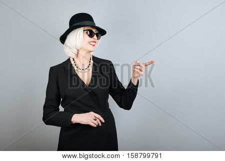 Good humor. Pretty overjoyed senior woman smiling and pointing on something while standing against isolated gray background. pointing on something.