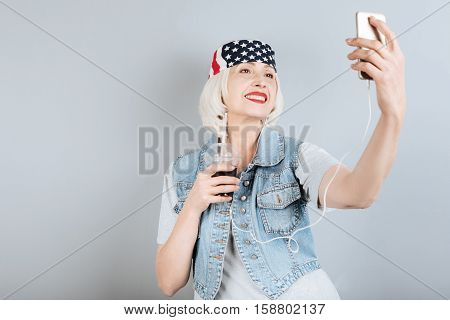 I love myself. Happy pretty senior woman holding cocktail and taking selfie while standing against isolated gray background.