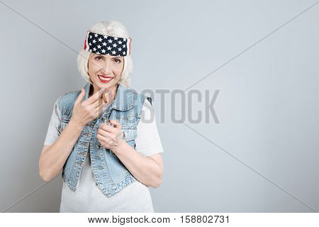 Simple rest. Overjoyed senior beautiful woman smiling and smoking while standing against isolated gray background.