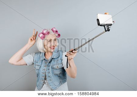 Modern technologies. Cheerful senior beautiful woman using headphones and taking selfie while standing against isolated gray background.