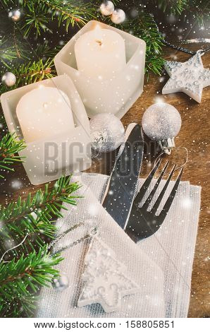 Table Place Setting for Christmas Eve. Winter Holidays. Christmas background. Festive Evening. Cutlery on napkin candles and fir branches. Selective focus. Toned image. Snow effect.