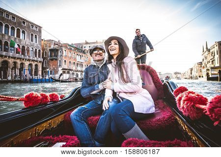 Couple of lovers on vacation in Venice Italy - Tourists having a trip on a venetian gondola