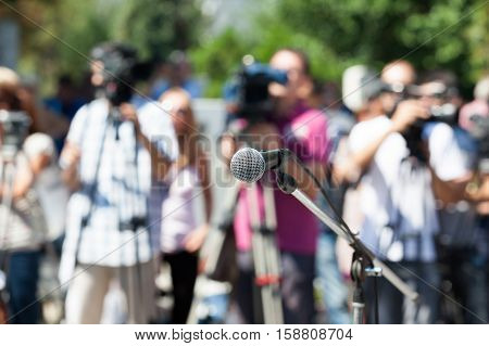 Microphone in focus against blurred camera operators and reporters