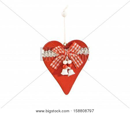 Vintage wooden Christmas decoration in the shape of heart with ribbons and bells isolated over white. Main colors are red and white.