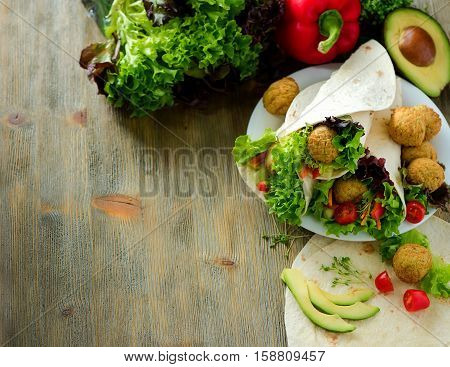 Tortilla wrap with falafel avocado and fresh salad vegetarian healthy food vegan concept copy space