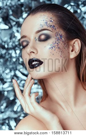 Sensitive beautiful young woman with evening shimmering makeup on christmas background. people, beauty, fashion, cosmetics, holiday and magic concept.