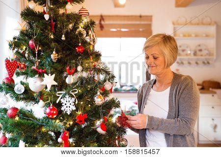 Beautiful senior woman decorating Christmas tree inside in her house.