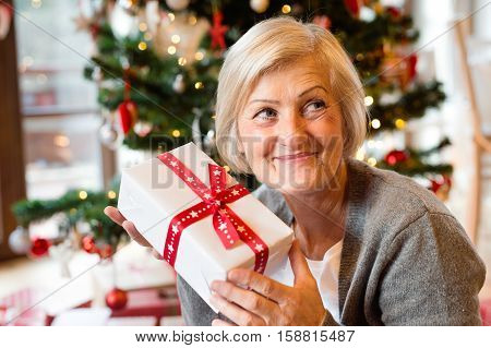 Beautiful senior woman sitting on the floor in front of illuminated Christmas tree inside in her house giving or receiving present.