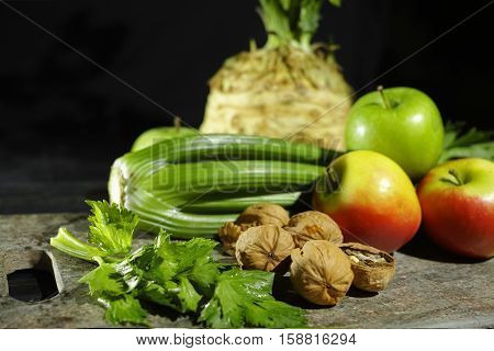 Ingredients for Waldorf salad - celery apples walnuts - fresh and healthy vegetables on granite board.