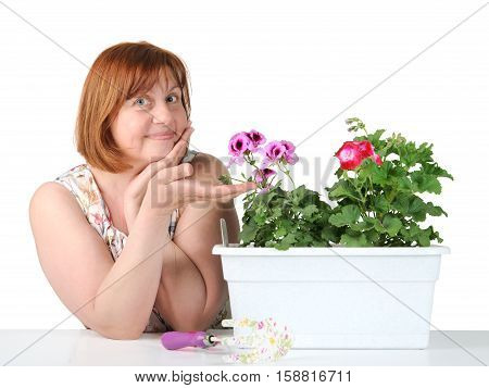 Portrait Of A Middle-aged Woman Showing A Houseplant..
