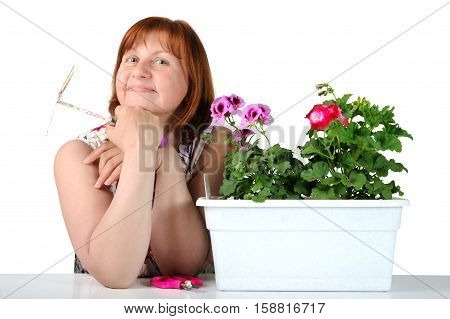 Portrait Of Pretty Middle-aged Woman With Pelargoniums In A Flower Pot..