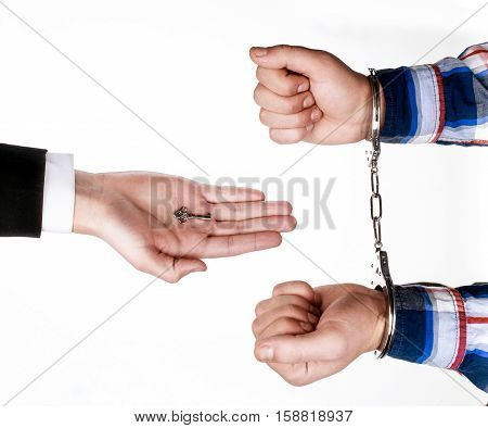 lawyer gives key of the handcuffs to prisoner, isolated on white.