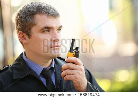Male security guard on light background outdoor