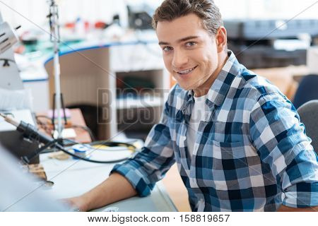 Repair process. Young handsome ambitious man sitting in a workroom while smiling and repairing drones