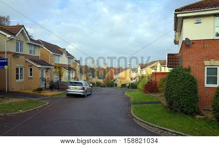 Bracknell,England - November 23, 2016: Homes on a modern housing estate with parked cars and a church bell tower in the distance in Bracknell, England