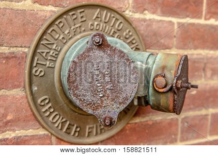 Worcester, MA, USA, 08 Aug. 2009: Vintage wall hydrant fire supply on red brick wall.
