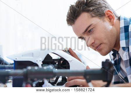 Interesting process. Concentrated handsome young man putting together drone details while sitting in workroom and enjoying his hobby.