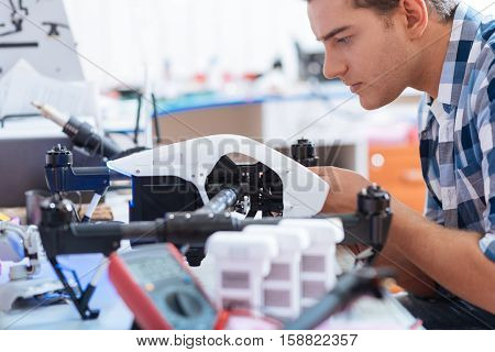 Keep it ready. Young concentrated handsome man repairing drone and using different equipment while controlling the process with electronic tester.