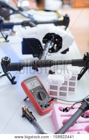 World of technology. Close up of table full of different repairing equipment such as wires and electronic tester and drone details lying on a white background.