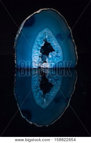 Polished blue amethyst. Stone with a cave of chrystals in the center. Mirroring in black background.